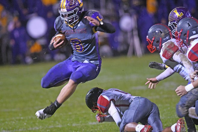 Lexington's Cade Stover leaps over a defender Friday night during a game with South Canton.