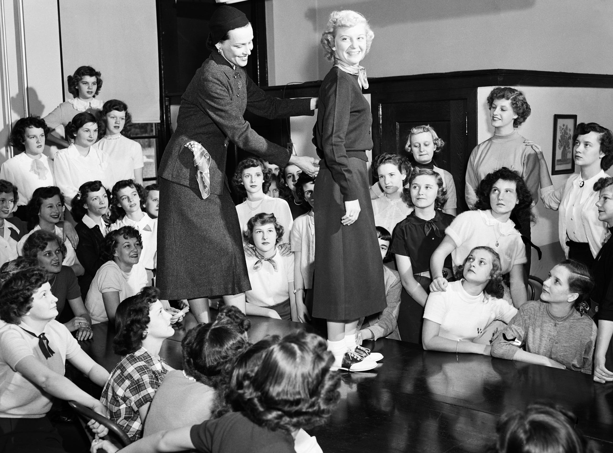 In the Home Economics section of Career Day at Tech High School on 25 Oct 1951, Mrs. Owen Massie of The Looking Glass, a modeling school, shows how the sweater fits Glynda Pruette of 2761 Burns.  Students are allowed to choose sessions on a variety of subjects, ranging from crime prevention to art.  Former graduates of Tech often discuss their field with students.  The Career Day observance is part of the school's vocational guidance program.