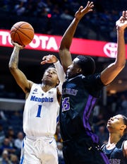 Memphis guard Tyler Harris (left) drives to the basket against LeMoyne-Owen defender Kemar Campbell (right) during action of their exhibition game at the FedExForum.