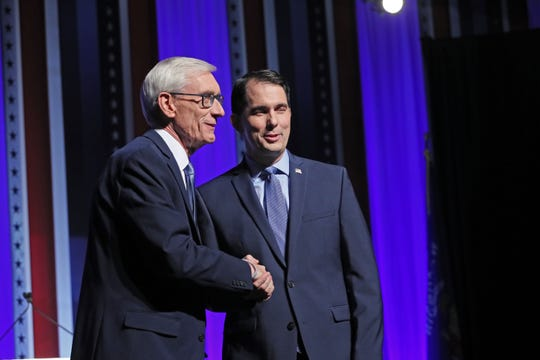 Gov. Scott Walker (right) and challenger Tony Evers meet on stage for introductions and photos before a 2018 debate at the University of Wisconsin-Milwaukee.