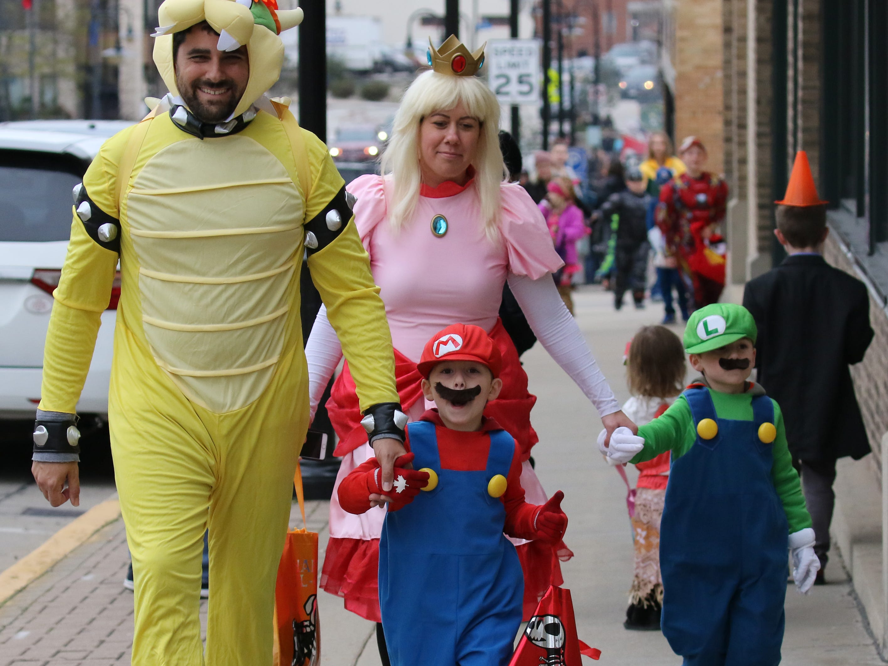 The Brandts, Zach (left), Brittany, Quinton and Brayden (right) all dress for the Menomonee Falls Downtown Trick or Treating on Oct. 25.