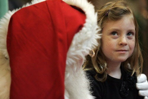 Amanda Shaw, 5, of Delafield, pauses to think for just a moment when Santa asked her a very important question when she visited with the Jolly ol' Elf at Brookfield Square on Dec. 1, 2009.