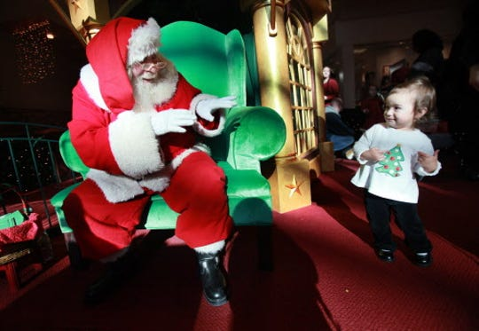 Victoria Acosta, 16-months-old, of Milwaukee, is thrilled to see Santa, but not sure how close she feels comfortable getting to him, as she visits him at Brookfield Square Mall, December 16, 2009.