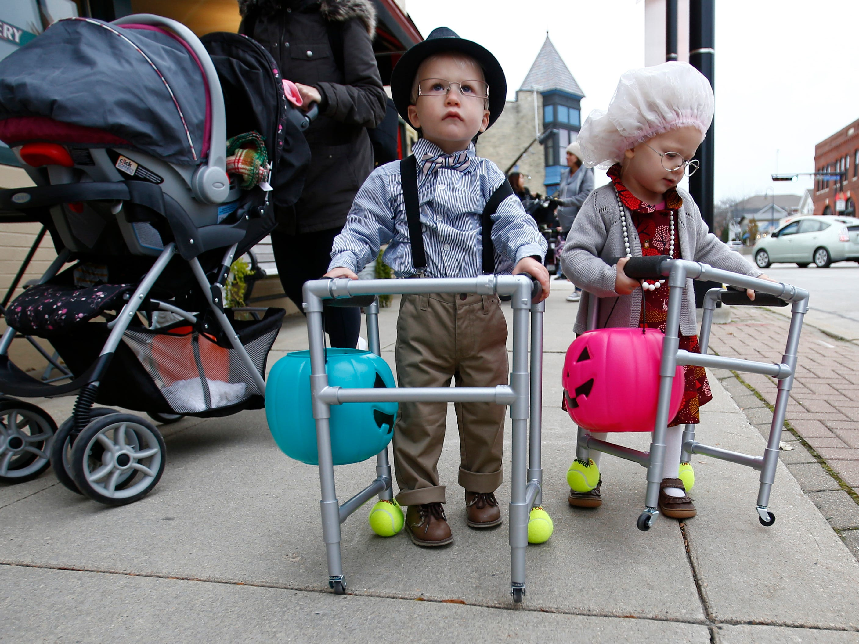 Twins Bennett and Abigail Rottier, 2, slowly make their way along Main Street during the Menomonee Falls Downtown Trick or Treating on Oct. 25.