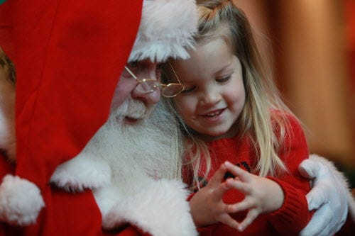In a quiet voice, Jaylin Gillstrom, 3, of Hartland, tells Santa that she'd like a castle for Christmas, while visiting him at Brookfield Square, Dec. 16, 2009. Santa has returned to the mall for the 2019 holiday season.