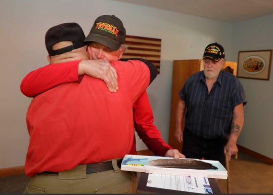 Larry Tallacus (left), a Native American, is hugged by Larry Cannon, a fellow member of the same platoon in Vietnam, after being presented with an eagle's feather. Tallacus and Jim Gales (right), of Glendale, recently found Cannon after 46 years and invited him to Gales' home.