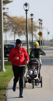 Matt and Mary Beth Stockton of Shorewood go for a morning run with their daughter Audrey, age 11 months, on parkland along Milwaukee's lakefront.