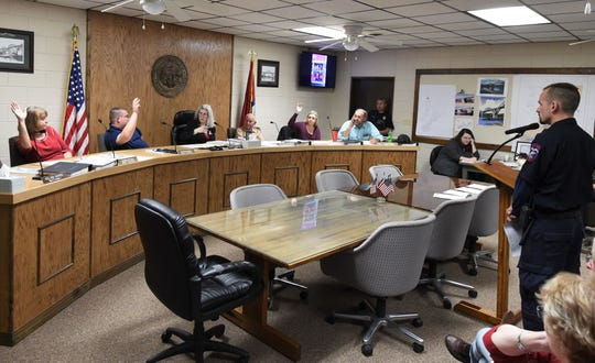 Members of the Cotter City Council raise their hands Thursday night to vote in favor of purchasing a used fire/rescue truck.