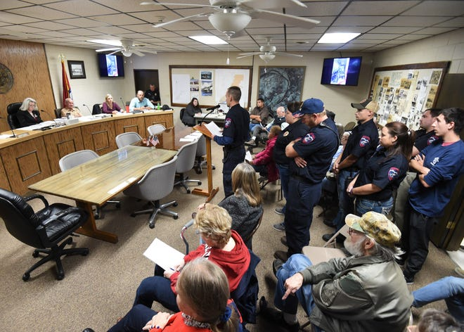 Members of the Cotter Fire Department (standing) fill the main aisle Thursday night night as Fire Chief Cory Swartz address the City Council about purchasing a used fire/rescue truck.