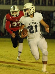 Siegel's Ethan Vanhook (21) runs during the first quarter as Cookeville's Cameron Harris (27) pursues during the Cavaliers' 42-8 win Thursday.