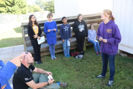 Alissa Whitney, president of the Thurman Francis Robotics Club, and other students practice their presentation for a recent robotics competition in front of parent volunteer Jonathan Harmon.