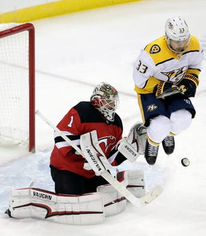 Nashville Predators right wing Viktor Arvidsson (33), of Sweden, jumps to get out of the way of a shot by a teammate as New Jersey Devils goaltender Keith Kinkaid (1) defends his net during the third period of an NHL hockey game, Thursday, Oct. 25, 2018, in Newark, N.J.