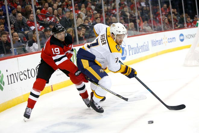 New Jersey Devils center Travis Zajac (19) and Nashville Predators defenseman Yannick Weber (7) battle for the puck during the second period at Prudential Center in Newark, N.J. on Thursday.