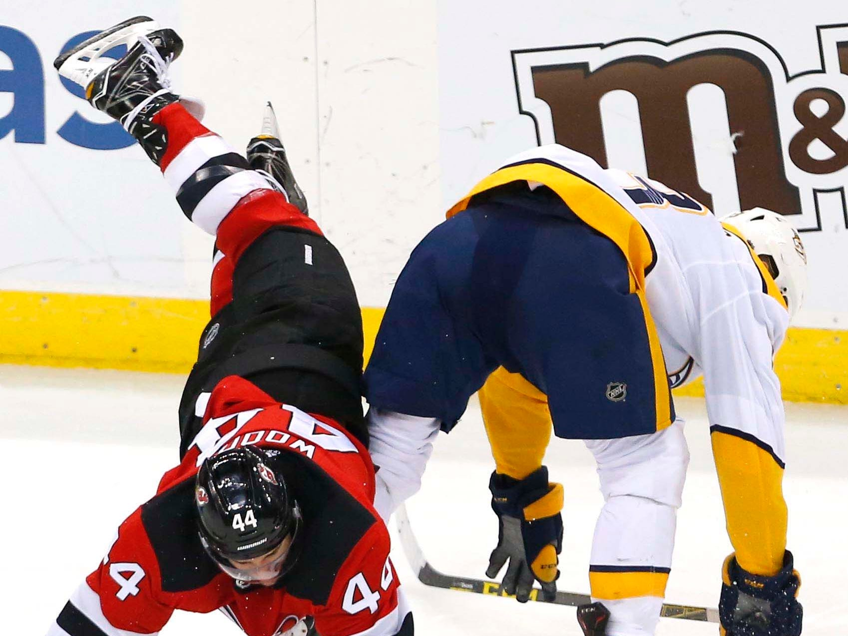 New Jersey Devils left wing Miles Wood (44) goes down after a collision with Nashville Predators center Nick Bonino (13) during the third  period at Prudential Center.