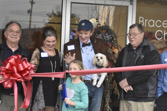 Dr. Jack Fisher holds Smiley, trained to calm nervous patients, stands with wife Debbie Fisher, Ashland City Mayor Rick Johnson and others at the Oct. 26 ribbon-cutting event for his new Artistic Smiles Orthodontics location. Johnson's granddaughter Danielle Sisco, 9, cut the ribbon.
