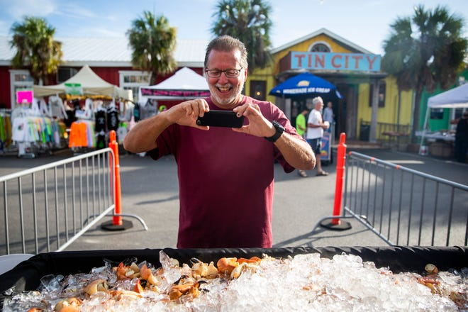 """Tom Foos of Cleveland, Ohio, takes a photo of stone crab claws during the fist day of the Naples Stone Crab Festival on Friday, October 26, 2018, at Tin City Shops in Naples. Foos, who travels to Naples for the festival with his wife every year, took the photo to send to friends and family in Ohio. """"They're gonna be so mad,"""" he said."""