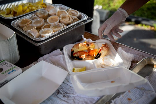Anthony Iandoli fills a to go box with stone crab claws during the fist day of the Naples Stone Crab Festival on Friday, October 26, 2018, at Tin City Shops in Naples.