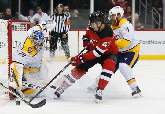 Oct 25, 2018; Newark, NJ, USA; Nashville Predators goaltender Juuse Saros (74) defends against New Jersey Devils center John Quenneville (47) during the second period at Prudential Center.