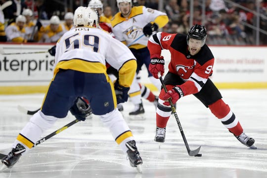 New Jersey Devils left wing Taylor Hall, right, attacks as Nashville Predators defenseman Roman Josi (59), of Switzerland, defends during the second period on Thursday.