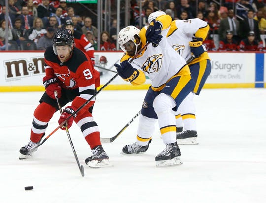 Oct 25, 2018; Newark, NJ, USA; New Jersey Devils left wing Taylor Hall (9) plays the puck against Nashville Predators defenseman P.K. Subban (76) during the second period at Prudential Center.