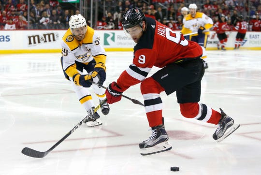 Oct 25, 2018; Newark, NJ, USA; Nashville Predators defenseman Roman Josi (59) and New Jersey Devils left wing Taylor Hall (9) battle for the puck during the second period at Prudential Center.