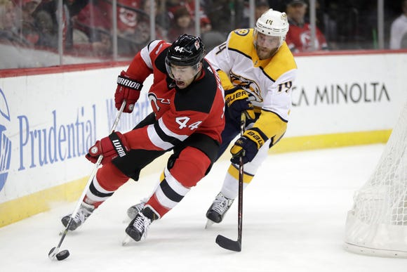 New Jersey Devils left wing Miles Wood (44) skates with the puck as Nashville Predators defenseman Mattias Ekholm (14), of Sweden, chases him during the second period of an NHL hockey game, Thursday, Oct. 25, 2018, in Newark, N.J.