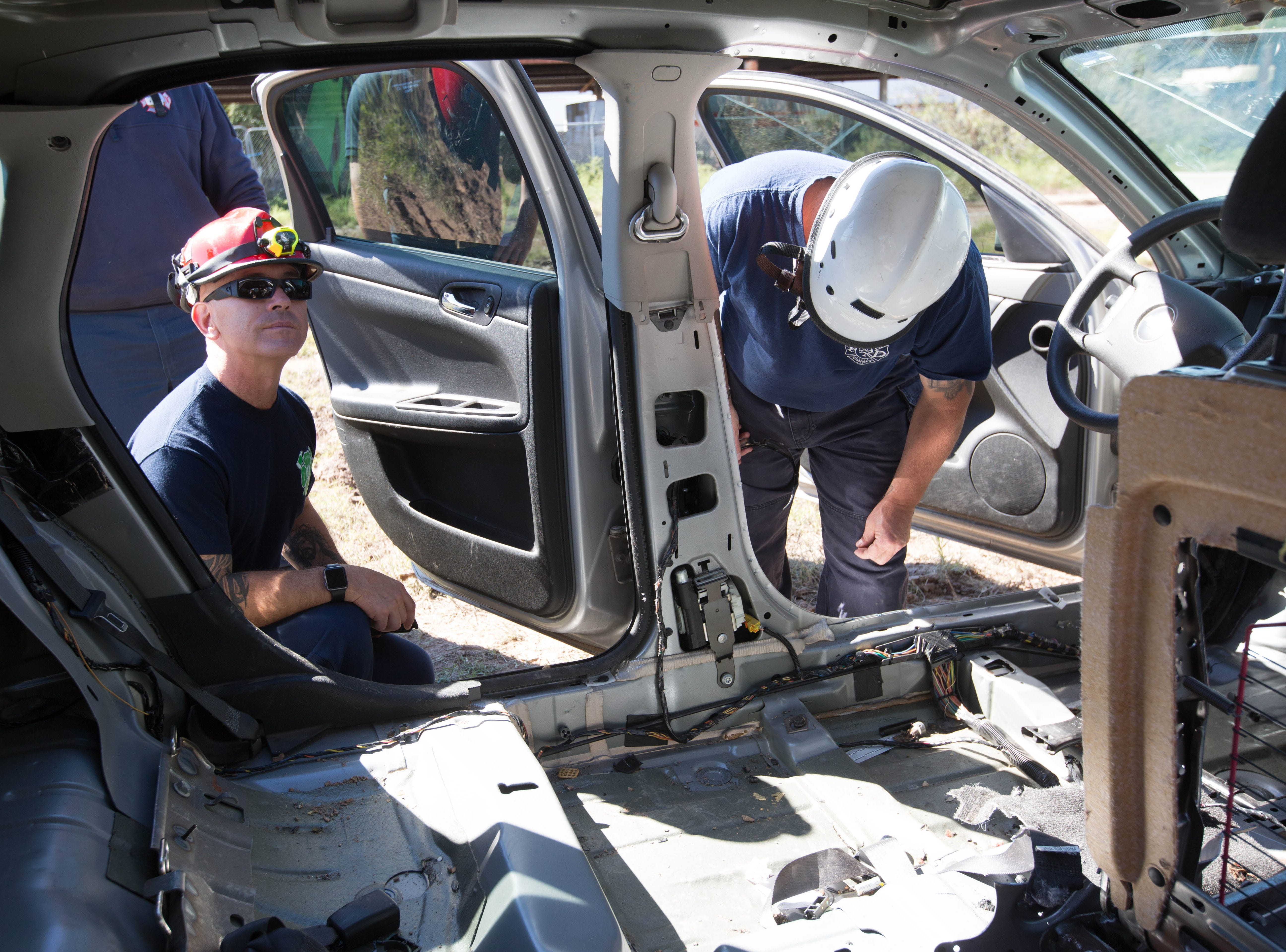 Chris Goodwin,  left, a firefighter from Albuquerque  Fire Rescue and Wayne Wendell, deputy chief from San Juan County Fire, look around a vehicle that has been stripped so firefighters can see the structure of a vehicle, getting an idea of areas they can cut or disassemble when they encounter them on the job, Friday October 26, 2018, during a three-day advanced auto extraction class.