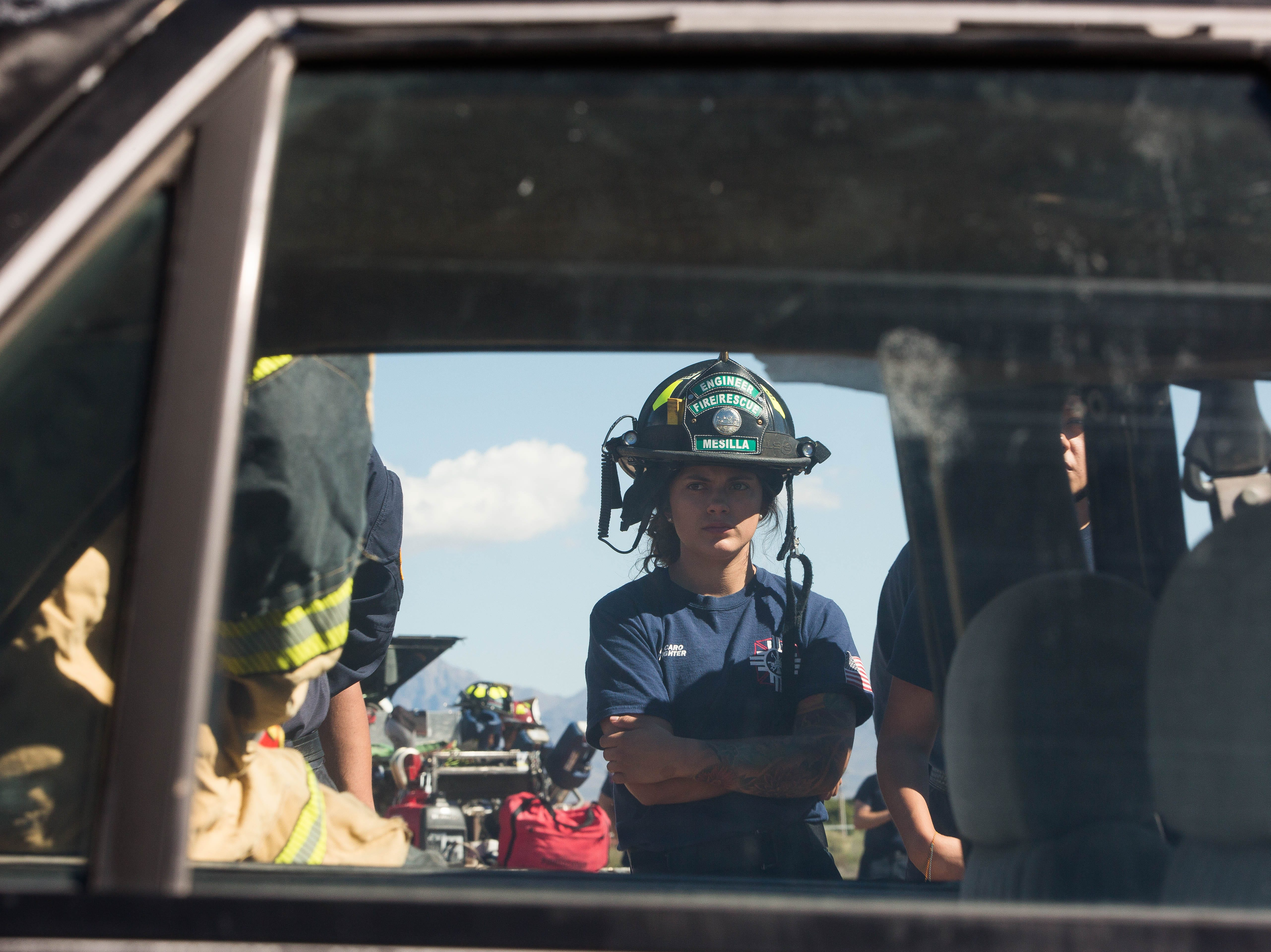 Ariel Caro, with Mesilla Fire department listens to Jeff Gates with Curtis Tool for Heroes, as he and two other instructors  demonstrate extraction tactics, Friday October 26, 2018. This demonstration is part of a three-day advanced auto extraction class, providing first responders with training different types of vehicles and accidents they will encounter while on the job.