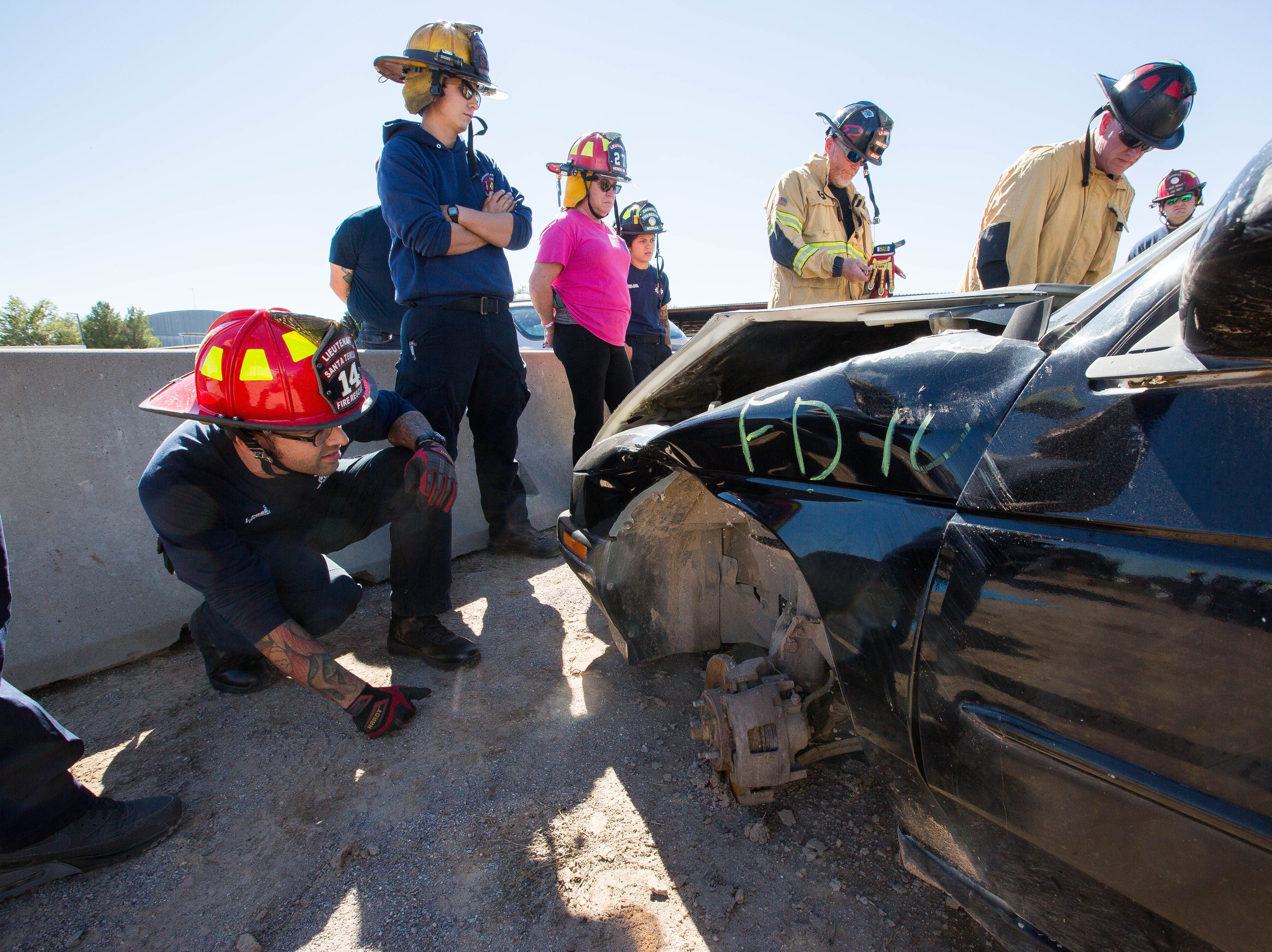 Eric Porras, lieutenant with the Santa Teresa Fire Department, watches as instructors from Curtis Tools for Heros and Hurst Jaws of Life, show firefighters basic technique for extraction tactics, Friday October 26, 2018. This demonstration is part of a three-day advanced auto extraction class, providing first responders with training different types of vehicles and accidents they will encounter while on the job.