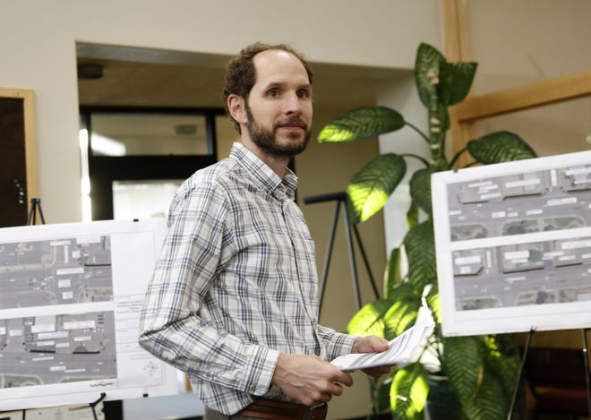 Project manager Darren Stewart of Russell Planning & Engineering displays plans for construction on 20th Street during a public meeting Thursday at Farmington City Hall.