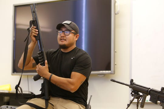 Diné College campus security officer Cherokee Dee shows a shotgun to participants during a training session about active-shooter incidents on Friday at the college's south campus in Shiprock.