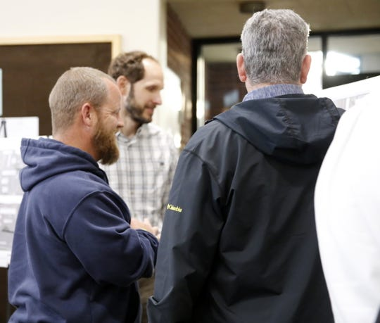 Farmington Electric Utility System senior distribution estimator Tim Henson, left, and Russell Planning & Engineering project manager Darren Stewart talk with a business owner Thursday about future construction on 20th Street during a public meeting at Farmington City Hall.