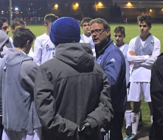 Detroit Catholic Central coach Gene Pulice addresses his team before the first overtime in Wednesday's Division 1-Regional 2 final.