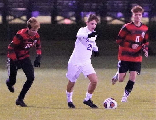 Catholic Central's Ben Kirouac (21) manuevers through Grand Blanc defenders Jeron Body (left) and Connor Shea (11) during Thursday's Division 1 regional final.
