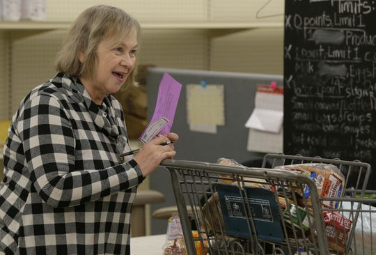 Vicki Pongratz works the checkout line Wednesday, Oct. 24, 2018, at the Oshkosh Area Community Pantry. Pongratz volunteers and uses the pantry, which serves over 2,000 families each month.