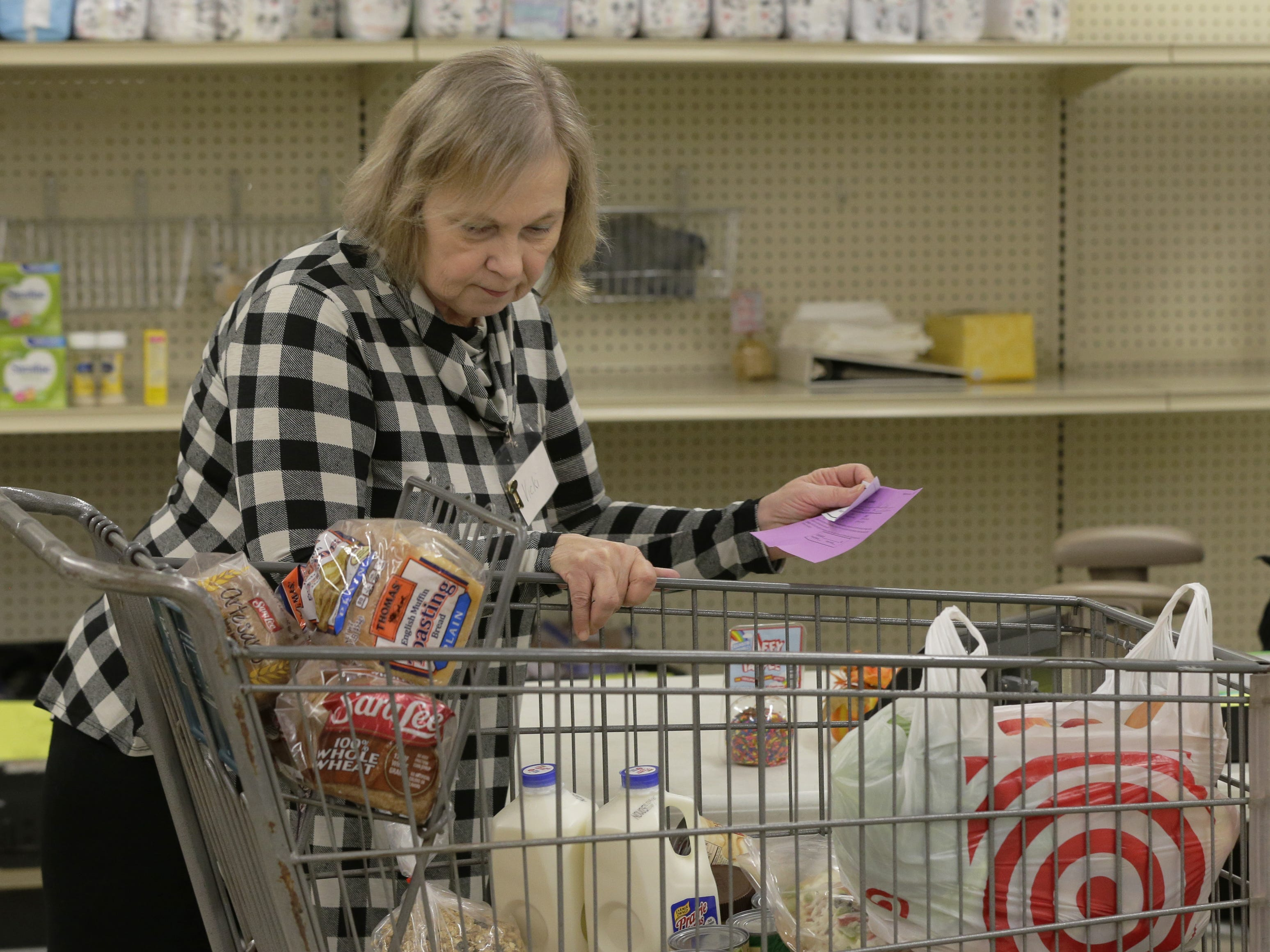 Vicki Pongratz reviews the contents of a cart while manning the checkout line Wednesday, Oct. 24, 2018, at the Oshkosh Area Community Pantry. Pongratz volunteers and uses the pantry, which serves over 2,000 families each month.