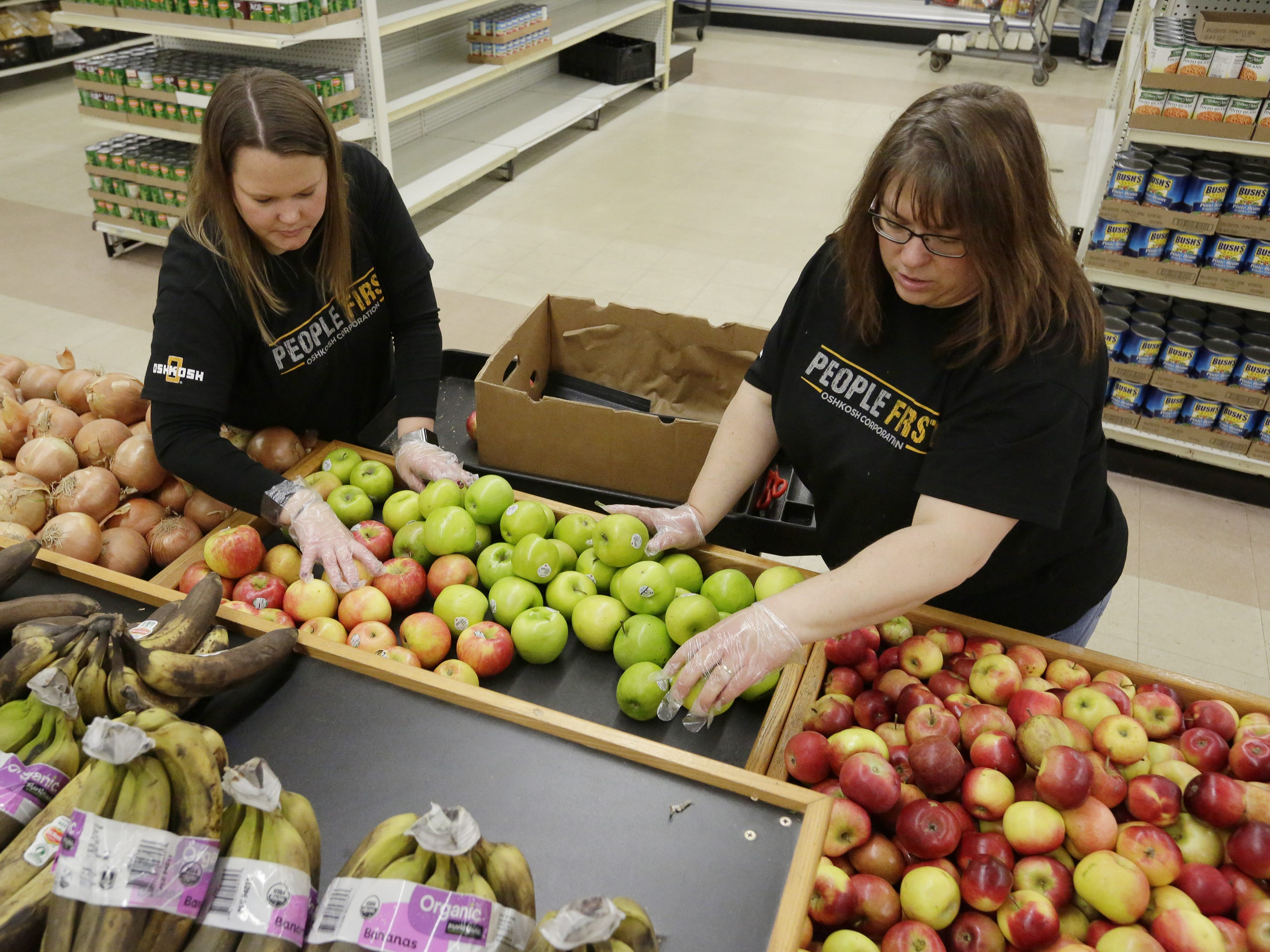 Volunteers Adrienna Bartell and Christine Heiser of Oshkosh Defense sort apples Wednesday, Oct. 24, 2018, at the Oshkosh Area Community Pantry. Over 2,000 families use the pantry each month.