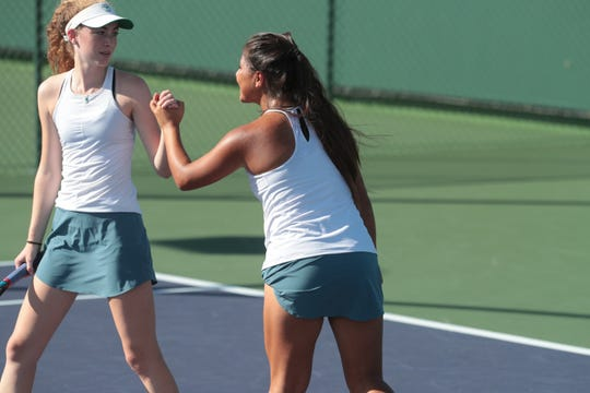 Maddy Woodforde, left, and Bella Perezchica celebrate after a point in the Desert Empire League tennis championship, Thursday, October 25, 2018.