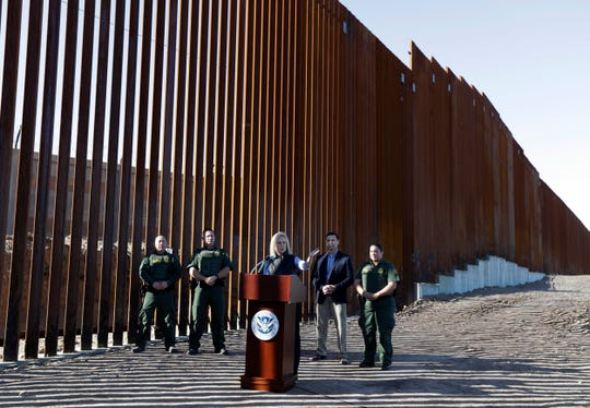 U.S. Department of Homeland Security Secretary Kirstjen Nielsen, center, speaks in front of a newly fortified border wall structure Friday, Oct. 26, 2018, in Calexico, Calif. (AP Photo/Gregory Bull)