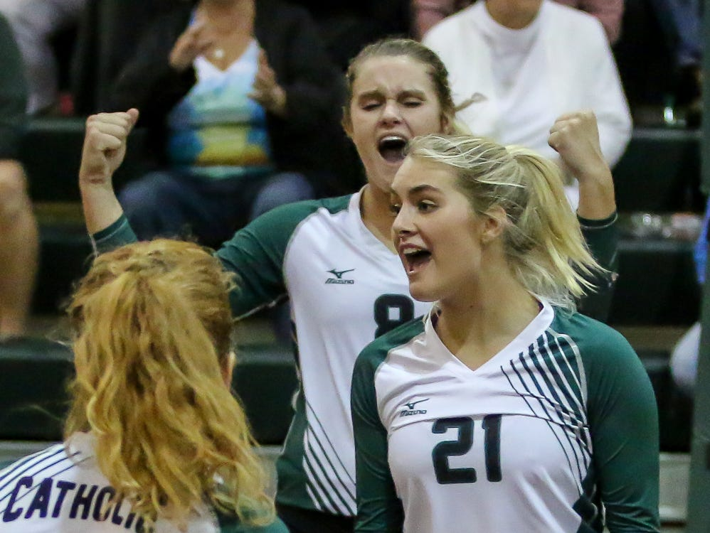 Pensacola Catholic's Terra Warrington (8), Hannah Meyers (17), and Molley Majewski (21) celebrate after Majewski scored a point against Marianna in the Region 1-5A quarterfinal game at Catholic High School on Thursday, October 25, 2018. The Crusaders defeated the Bulldogs in three straight sets and will face Florida High next week in the region semifinal game.