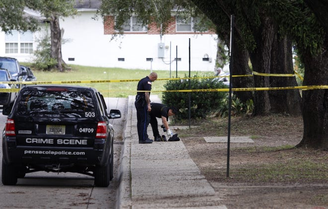 Pensacola police investigators examine evidence at the scene of a shooting at Attucks Court on Friday.