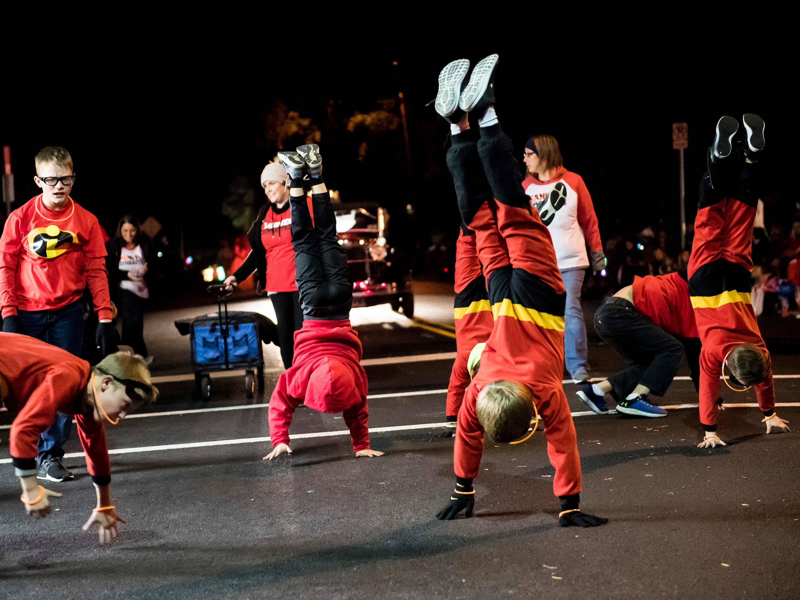 Hanover Gymnastics members do walking handstands down Baltimore Street during the 77th annual Hanover Halloween parade on Thursday, October 25, 2018.
