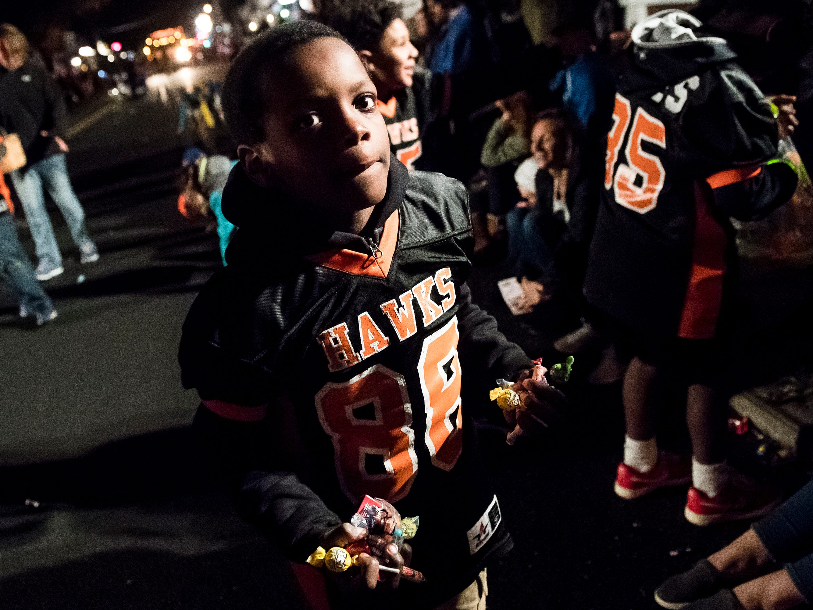 A young Hanover Nighthawk passes out handfuls of candy during the 77th annual Hanover Halloween parade on Thursday, October 25, 2018.