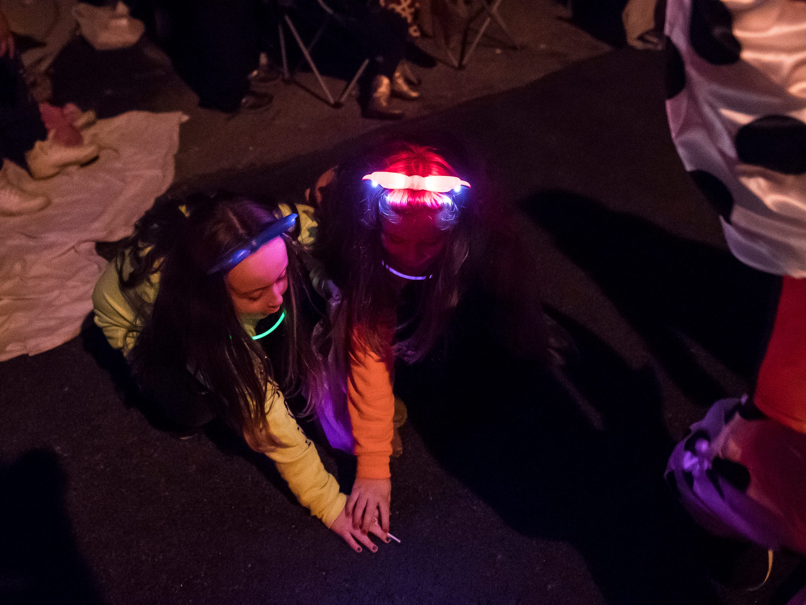 Two children reach for the same piece of candy during the 77th annual Hanover Halloween parade on Thursday, October 25, 2018.