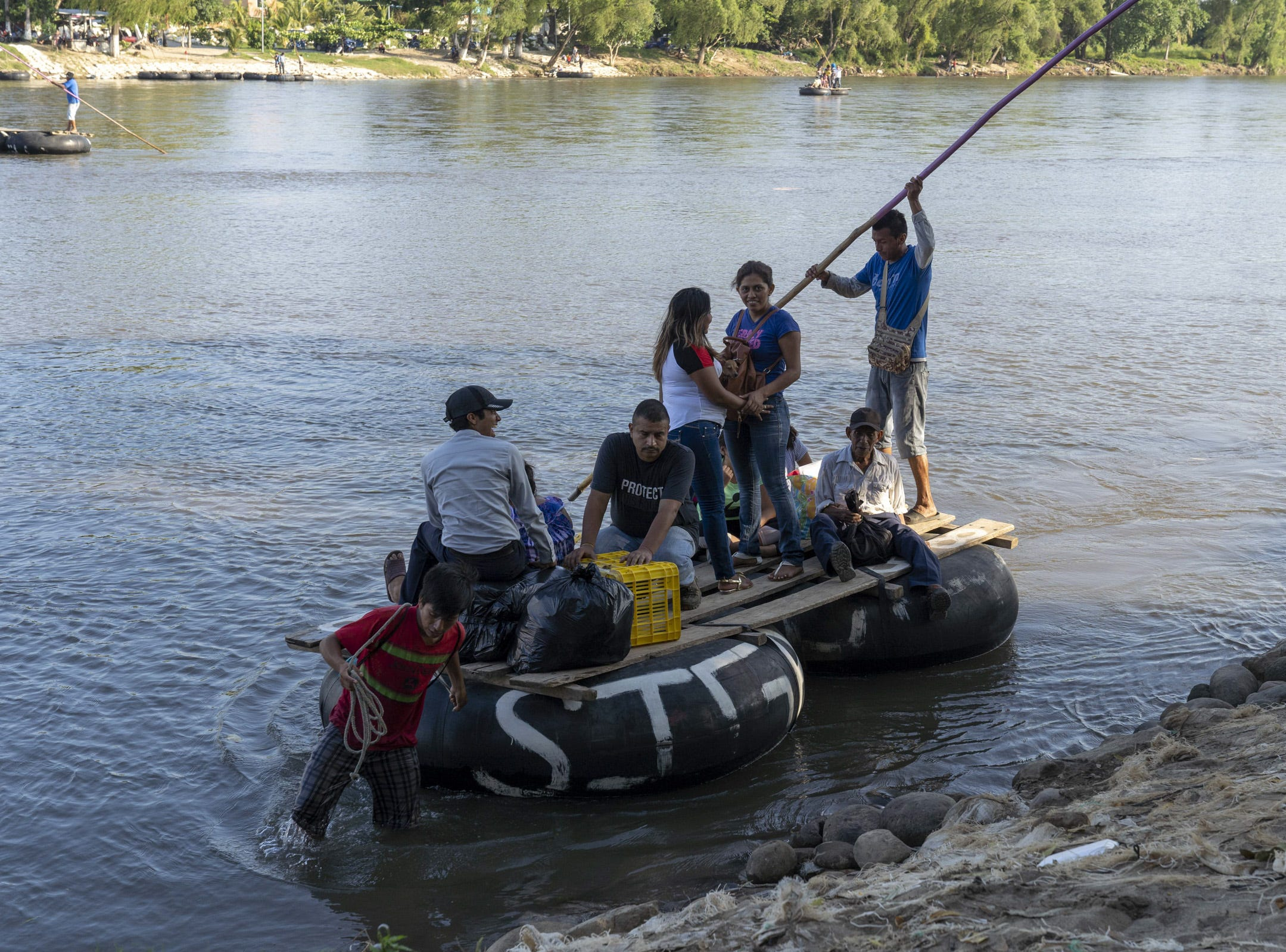 Border crossers from Guatemala pay money after crossing on a raft at Cuidad Hidalgo, Mexico.