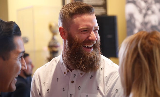 Diamondbacks' Archie Bradley laughs with organizers at the Fiesta Bowl Center before choosing a name of a teacher to call and tell that she won $5,000 for their classroom in Scottsdale, Ariz. on October 25, 2018.
