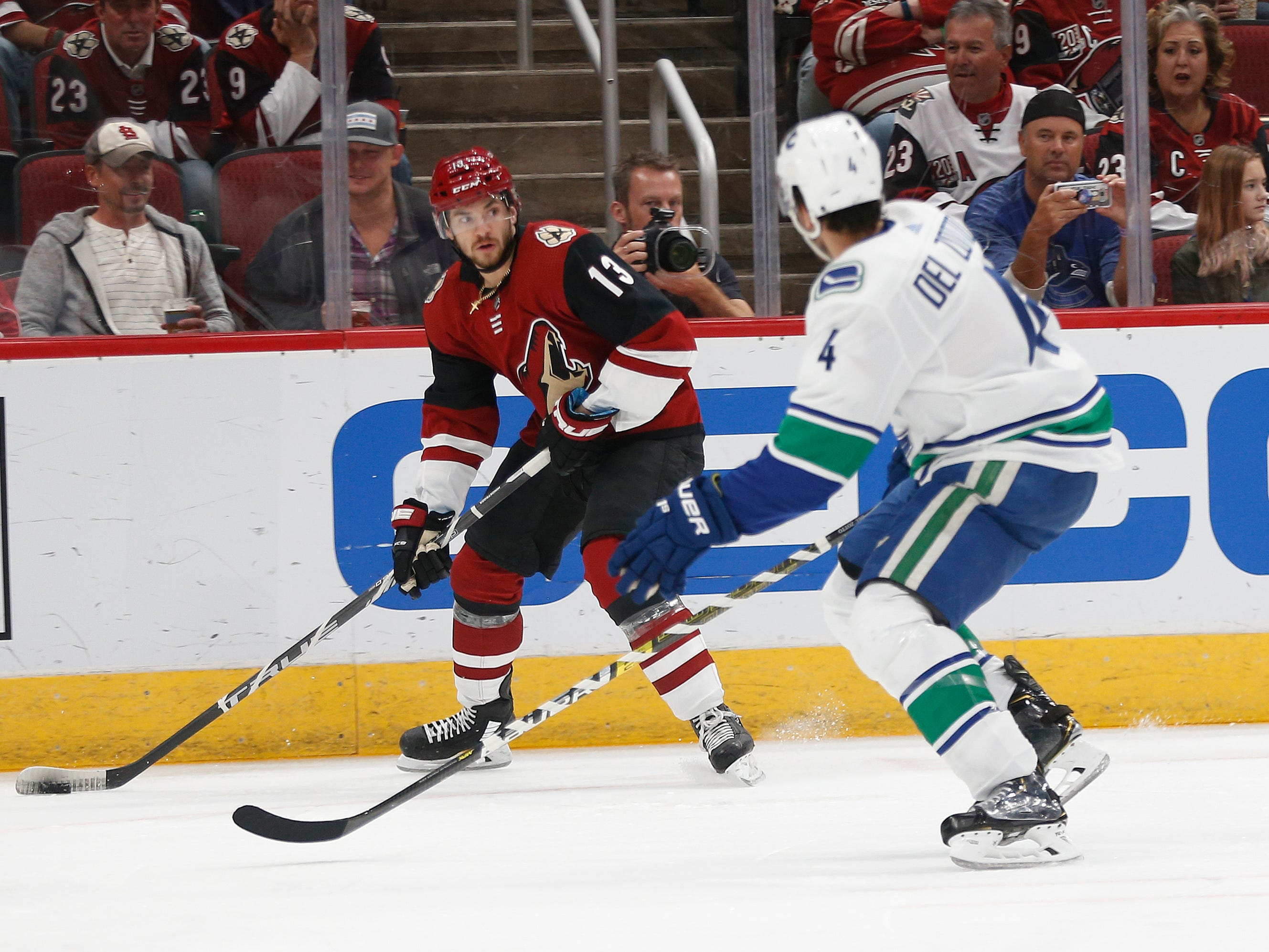 Coyotes' Vinnie Hinostroza (13) passes the puck against Canucks' Michael Del Zotto (4) during the first period at Gila River Arena in Glendale, Ariz. on October 25, 2018.