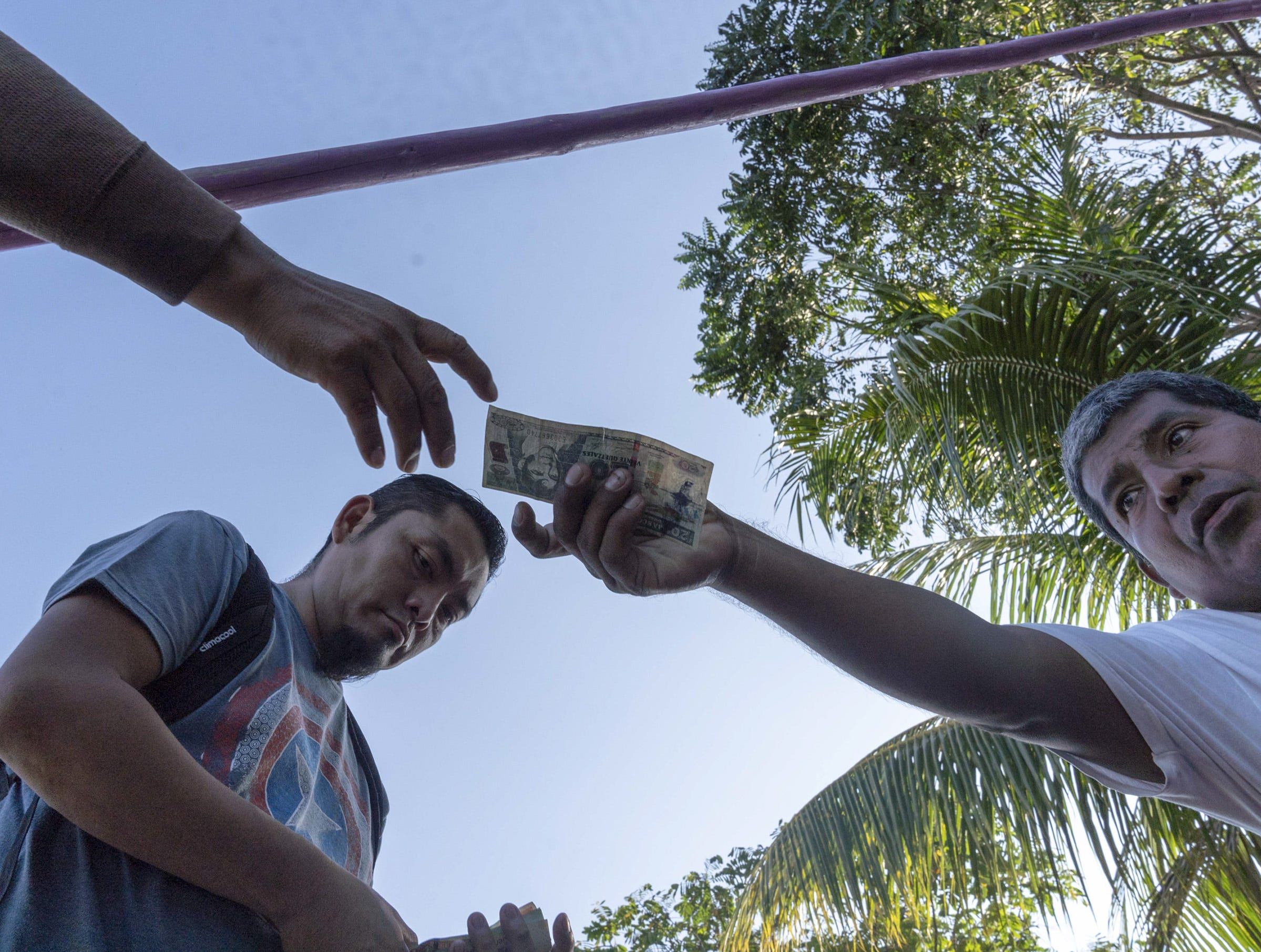 Border crossers from Guatemala pay money after crossing in a raft at Cuidad Hidalgo, Mexico.
