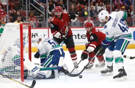 Coyotes forward Brad Richardson (15) tries to knock the puck past the Canucks during a game at Gila River Arena on Oct. 25.