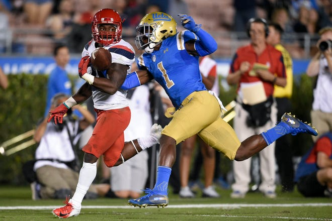 Oct 20, 2018: UCLA Bruins defensive back Darnay Holmes (1) knocks the ball away from Arizona Wildcats running back J.J. Taylor (21) for a fumble during the first half at Rose Bowl.